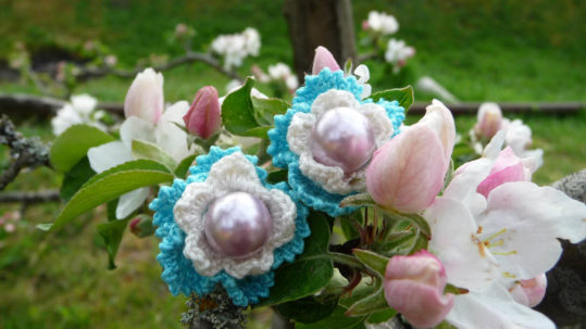 crochet earrings in a tree with spring apple blossoms