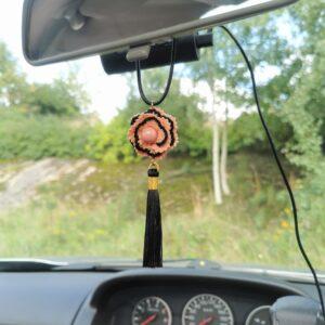car pendant with orange crochet flower and black tassel